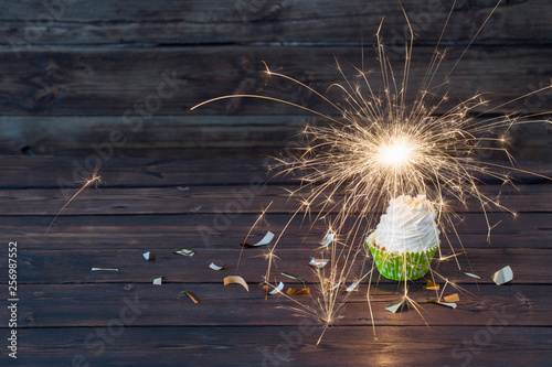 Fotografía birthday cake with sparkler on old wooden background