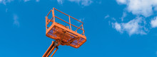 Cherry Picker On Blue Sky Background. Boom With Lift Bucket Of Heavy Machinery. Platform Of The Telescopic Construction Lift Close-up.