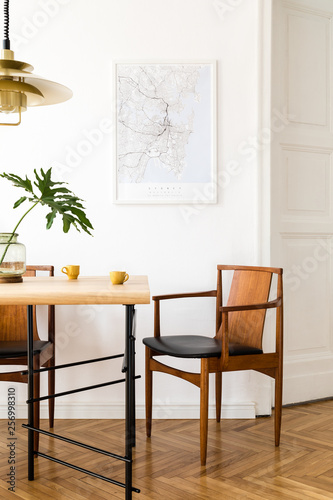 Fotografia, Obraz  Stylish and modern dining room interior with mock up poster map, sharing table design chairs, gold pedant lamp and cups of coffee