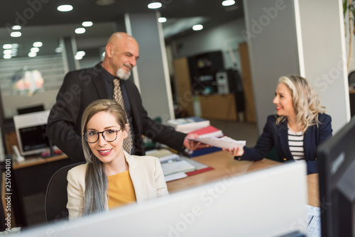 Photo  woman in office looking at camera with people working in background