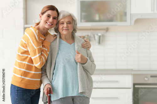 Obraz Elderly woman with female caregiver in kitchen. Space for text - fototapety do salonu