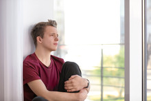 Upset Teenage Boy Sitting Alone Near Window Indoors