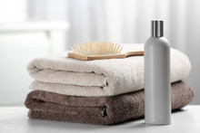 Towels With Hair Brush And Shampoo On Table