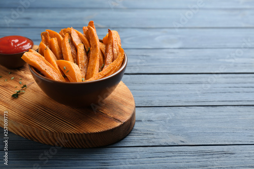 Bowl with tasty sweet potato fries on wooden background, space for text Fototapeta