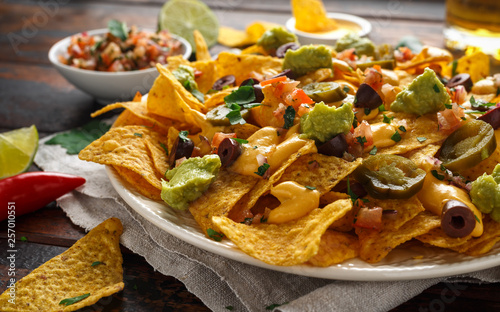 Fényképezés  Mexican nachos tortilla chips with olives, jalapeno, guacamole, tomatoes salsa, cheese dipand beer
