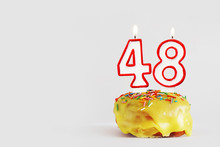 Forty Eight Years Anniversary. Birthday Cupcake With White Burning Candles With Red Border In The Form Of Number Forty Eight. Light Gray Background With Copy Space