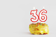 Thirty Six Years Anniversary. Birthday Cupcake With White Burning Candles With Red Border In The Form Of Number Thirty Six. Light Gray Background With Copy Space