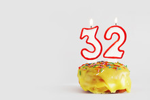 Thirty Two Years Anniversary. Birthday Cupcake With White Burning Candles With Red Border In The Form Of Number Thirty Two. Light Gray Background With Copy Space