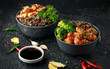 Teriyaki chicken, steamed broccoli and wild rice served in two Asian clay bowls