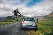 Man Jumping On The Car In The Mountains
