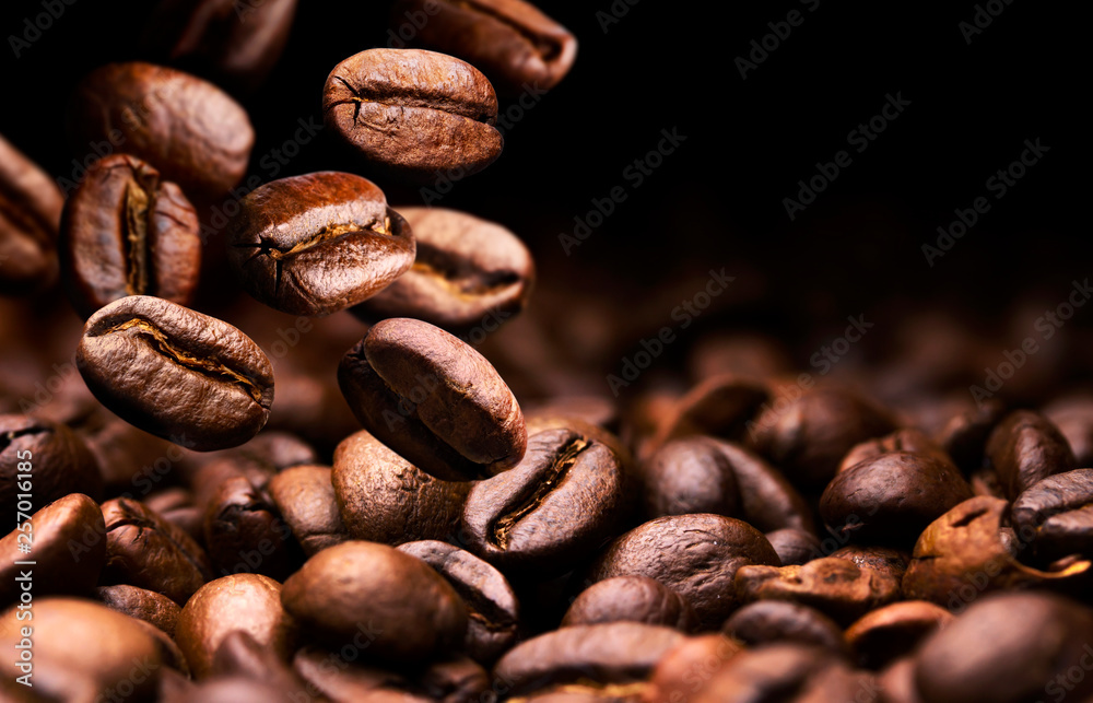 Coffee beans falling on pile, black background with copy space, close up