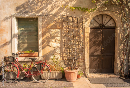 Foto  Exterior of ann old, abandoned house with a red bicycle and potted plants in a s