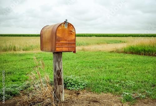 Fototapeta  An old rusty mailbox in a field.
