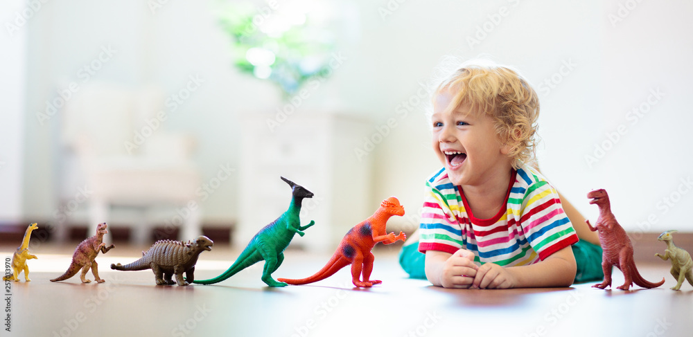 Fototapety, obrazy: Child playing with toy dinosaurs. Kids toys.
