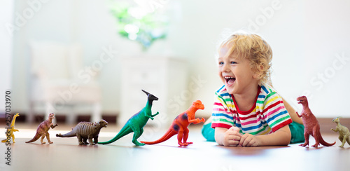 Obraz Child playing with toy dinosaurs. Kids toys. - fototapety do salonu