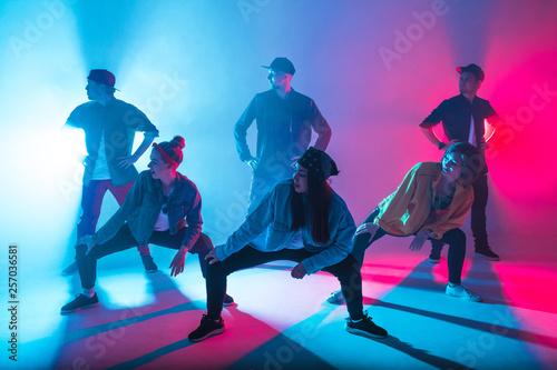 Slika na platnu Group of diverse young hip-hop dancers in studio with special lighting effects i