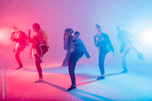 Photo Group of diverse young hip-hop dancers in studio with special lighting effects i