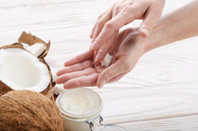 Coconut Oil On Human Palm And In Airtight Glass Jar With Shell Pieces Aside On White Wooden Table