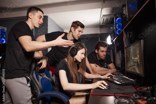 Obraz na płótnie Young woman playing computer game in club and her friends supporting her and cheering, standing behind