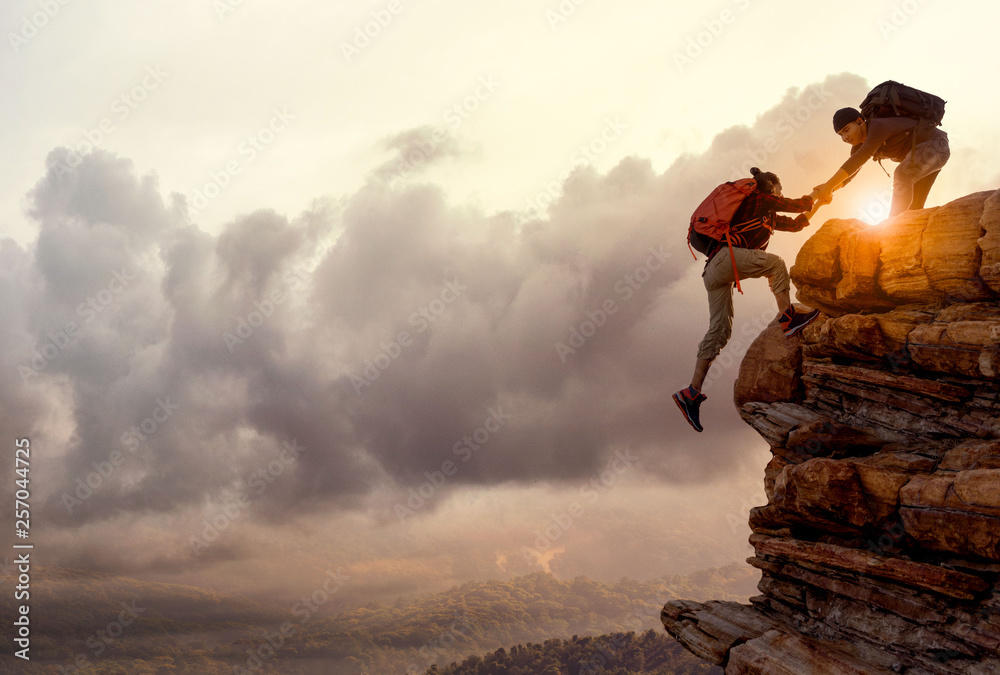 Fototapety, obrazy: People helping each other hike up a mountain at sunrise. Giving a helping hand, and active fit lifestyle concept.Asia couple hiking help each other.