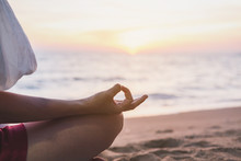 Young Woman Practicing Yoga On The Tropical Beach At Sunset
