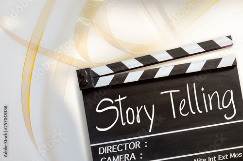 Photo  Story telling text title on movie clapper board and 8mm film reel on white backg