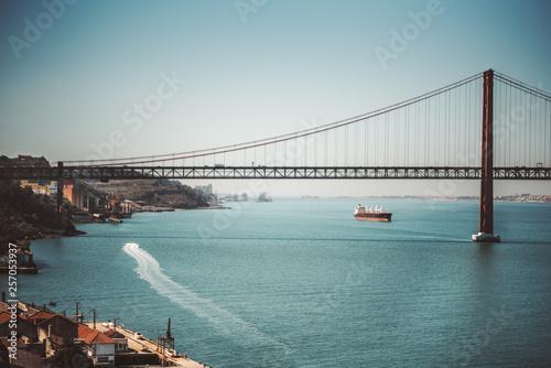 """Fototapeta premium Piękne krajobrazy z ogromnym wiszącym mostem """"Ponte 25 de Abril"""" nad rzeką Tag w Lizbonie, Portugalia w ciepły słoneczny dzień z dwoma statkami, z których jeden pozostawia długi ślad na wodzie"""