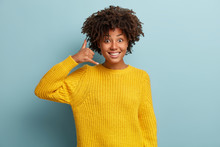 Smiling Delighted Black Woman Makes Phone Gesture, Shows Call Me Back Sign With Hand Near Ear, Pretends Talking On Mobile Phone, Dressed In Yellow Clothes, Has Glad Expression, Poses Indoor.