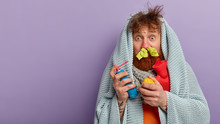 Problems With Health Concept. Puzzled Redhead Bearded Man Stares With Bugged Eyes, Holds Aerosol Against Cough, Hot Water Bottle, Wrapped In Blanket, Has Flu, Receives Vitmanis From Fresh Lemon