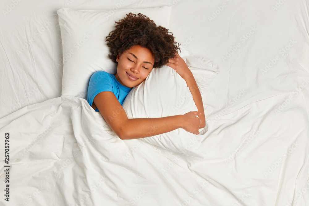 Fototapeta Satisfied pretty Afro American young woman has peaceful sleep, lies in bed on comfortable pillow, sees pleasant dreams, has gentle smile, enjoys softness of bedclothes, being under white blanket