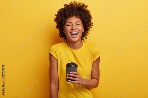 Monchrome shot of cheerful dark skinned woman laughs and talks casually, holds disposable cup of tea, wears yellow bright t shirt Canvas Print