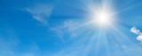Fototapeta Na sufit - In the blue sky bright sun and light clouds. Wide photo.