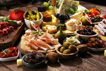Italian Antipasti Wine Snacks Set. Cheese Variety, Mediterranean Olives, Crudo, Prosciutto Di Parma, Salami And Wine In Glasses Over Grunge Background.