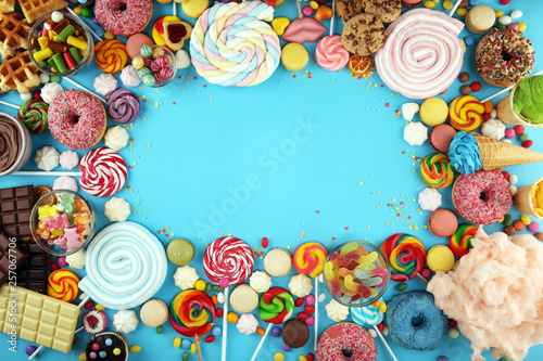 candies with jelly and sugar. colorful array of different childs sweets and treats on blue