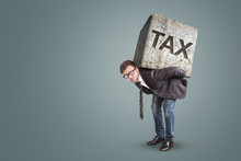 Businessman Carrying A Heavy Stone With The Word TAX On It