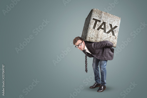 Fototapeta Businessman carrying a heavy stone with the word TAX on it obraz