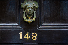 House Number 148 With The One Hundred And Forty Eight In Bronze On A Black House Door With A Door Knocker In The Form Of A Female Head
