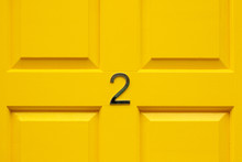 House Number Two With The 2 In The Middle Cross Bar Of A Bright Yellow Painted House Door