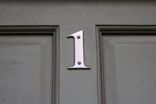 House Number One With The 1 In Elegant Silver Metal On The Middle Cross Of A Wooden House Door