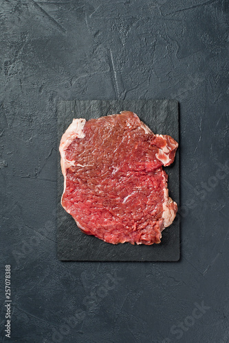 Staande foto Vlees Beef flank steak on a stone Board. Black background, top view, space for text
