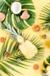 Tropical pattern, background with exotic fruits and tropical palm leaves on yellow background wite. Flat lay, top view