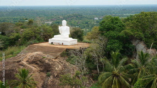 Fotografia  Mihintale, Sri Lanka Big white Buddha statue against blue sky in Mihintale, the