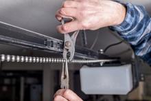 Home Garage Door Opener Chain Being Repaired By A Mechanic