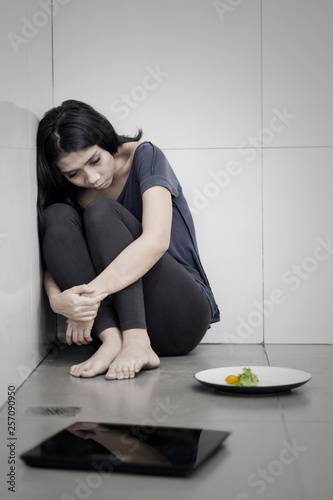 Sad woman with salad and weight scales Wallpaper Mural