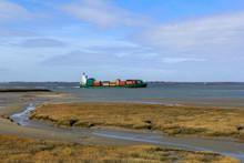 A Ship Sails Along The Salt Marsh Towards Antwerp In Springtime With A Blue Sky