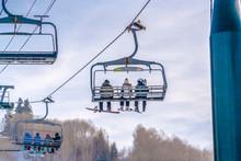 Skiers On Ski Lifts Against Sky In Park City Utah