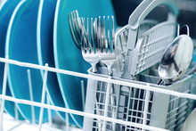 Kitchenware In Dishwasher Close-up, Focus On Basket With Spoons And Forks