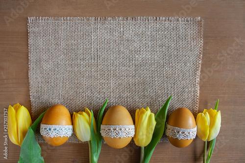 Obraz Wielkanocne tło - żółte pisanki i żółte tulipany na tkaninie z juty - fototapety do salonu