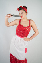 Beautiful Young Girl Standing In Red Polka Dot Pinup Dress And Apron, Holding A Big Knife And Picking Her Teeth Because The Food Is Stuck, On A White Studio Plain Background Alone