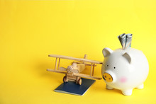 Piggy Bank With Toy Airplane And Passport On Color Background, Space For Text. Travel Agency